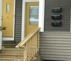 Photo of multi-unit residential buidling showing two front doors and multiple mailboxes at top of stairway